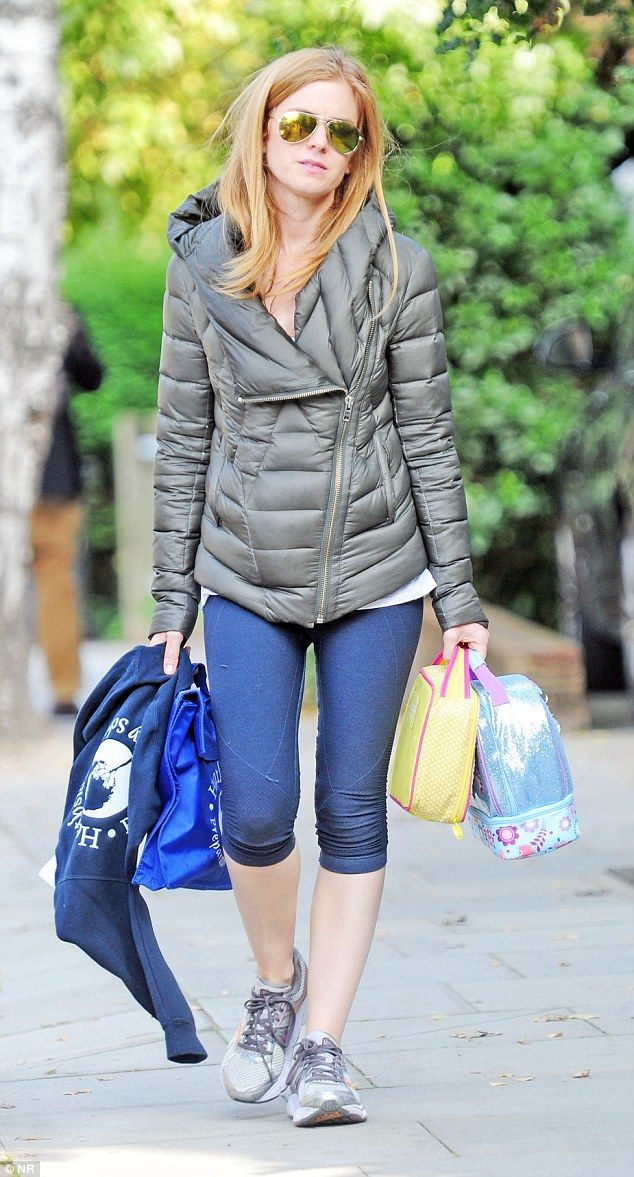 On the move: Actress Isla Fisher wore exercise gear and carried what looked like children'...