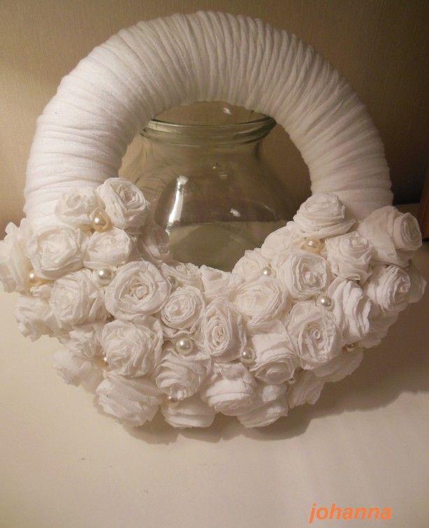 Krans omwikkelt met katoen garen , roosjes gemaakt van wit crêpepapier met de lijmpistool vastgezet en wat parels er tussen .
