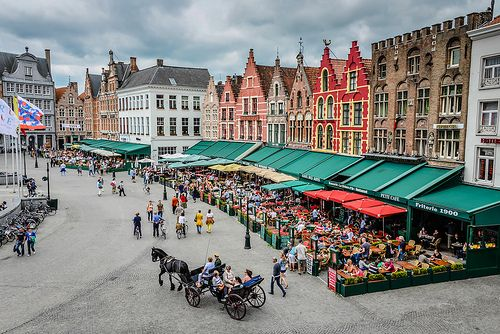"The Markt, Brugge: ""Come summer, the city's central cobblestone square is thronging with tourists and clattering horse-drawn carriages. The domain of the guildsmen, it was the commercial and social focal point of Brugge and today their gabled houses host the cafés and restaurants that flank two sides of the square."" Flanders: the Bradt Guide www.bradtguides.com"
