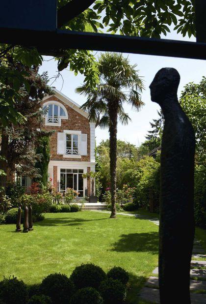 """Une meulière entre rosiers et palmier, sur laquelle veille la sculpture """"Lui"""""""