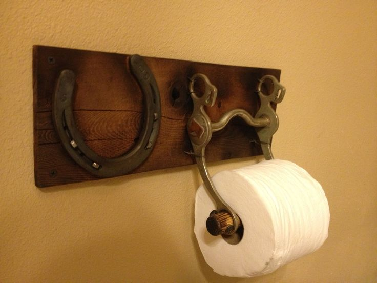 Toilet paper holder with an old horse bit and horse shoe.