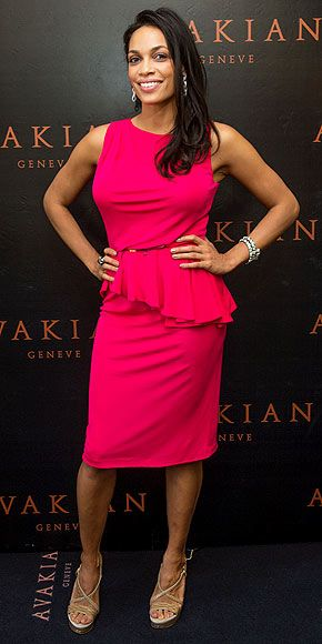 Rosario Dawson in an electric pink peplum dress, which she teams with neutral sandals and Avakian bling at the jewelry brands Cannes suite.