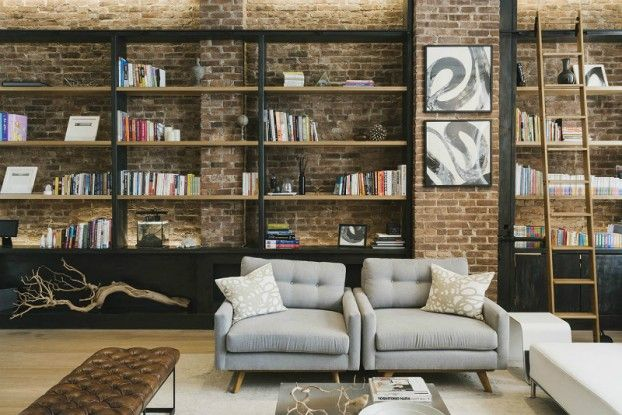 industrial living room with brick wall gray armchairs and black library