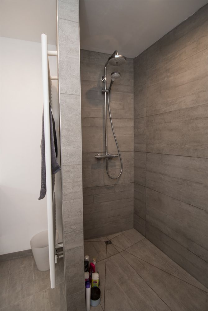Deze badkamer met schuine muur werd echt handig ingericht met een bad een ruim lavabomeubel en - Badkamer muur tegels porcelanosa ...