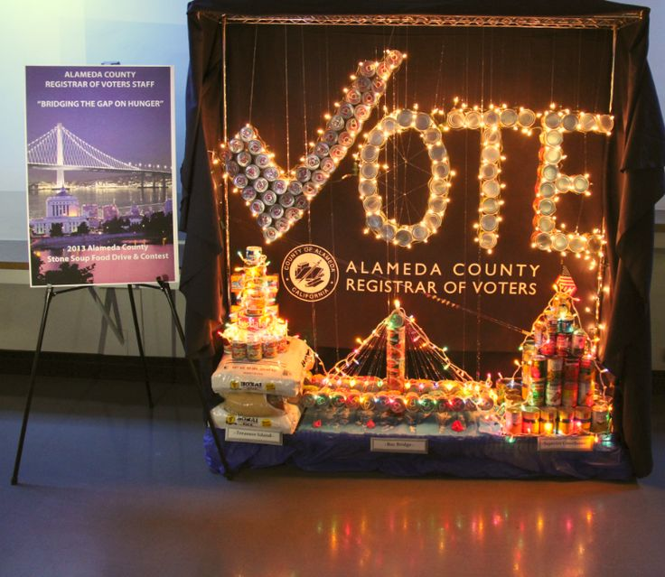 """Bridging the Gap on Hunger"" was the Alameda County Registrar of Voters theme for their display. The display reflects landmarks in Alameda County. Treasure Island (bottom left), the Bay Bridge (bottom center), and the Rene C. Davidson Superior Court House (bottom right) are depicted.  Above the landmarks, suspended in mid-air with fishing wire, are cans that spell out the word vote where the ""v"" in vote represents a red check mark. The department collected over 500 pounds of food."