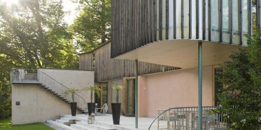 MIDDELHAVSHUS I HOVEDSTADEN: Den buete villaen i duse farger og rustikke materialer - pluss plast - er en ekte sommerperle ikke langt fra sjøen. Design av arkitekt, professor Knut Hjeltnes.