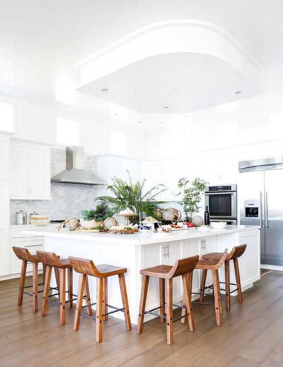 Beautiful white kitchen features an extra large white kitchen island topped with white quartz countertops surrounded on two sides by 6 carved wood counter ... & Best 25+ Wood counter stools ideas on Pinterest | Counter stools ... islam-shia.org