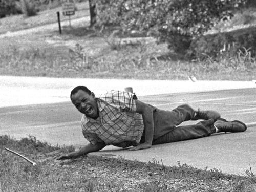 """Civil rights activist and the first African American to attend the University of Mississippi, James Meredith grimaces in pain as he pulls himself across Highway 51 after being shot in Hernando, Mississippi, June 6, 1966. Pulitzer Prize winning photo by Jack Thornell, see comment. [[MORE]] The shooter was a man called Aubrey Norvell, who had reportedly shouted, """"I just want James Meredith!"""" Miraculously, none of the sixty-three birdshot pellets struck a vital organ or broke Meredith's spine…"""
