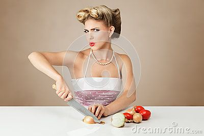 Young blonde woman cutting onion in kitchen