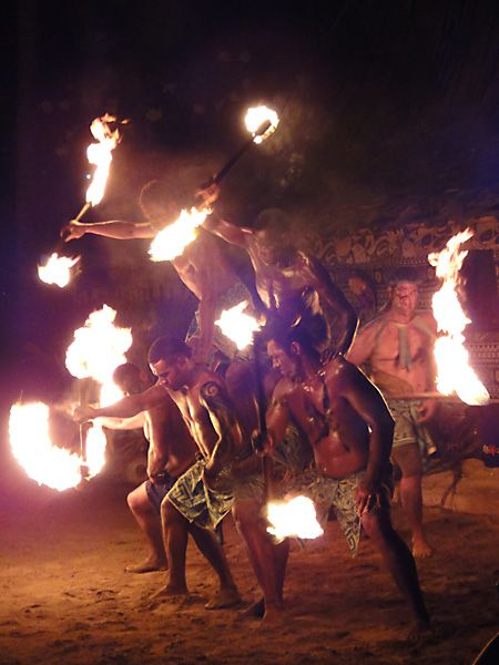 Fijian dancers form a human pyramid while spinning fire