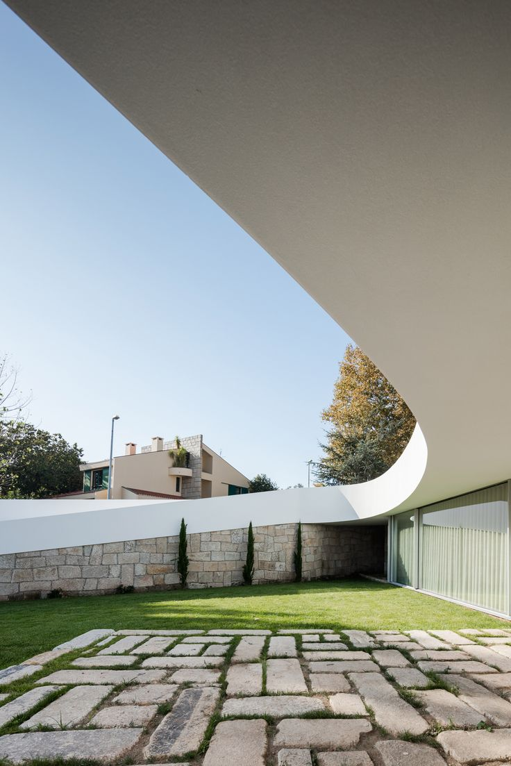 This house in Portugal, designed by architecture studio NOARQ, features a large curving canopy that wraps around a south-facing patio.