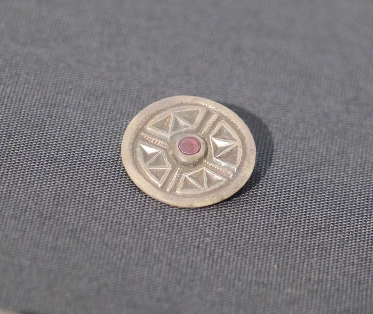 Grave goods from the 7thC Anglo-Saxon cemetery at Saltwood, Kent. Grave 1. Cast silver brooch with central garnet. Photograph courtesy of Lindsay Kerr.