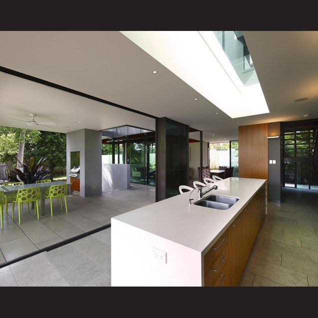 Large stacking doors on two sides open up this kitchen to an expansive terrace with a built-in barbecue and alfresco dining area.