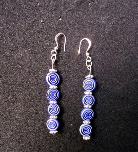 Spiral - 14     Långa örhängen i silverpläterad metall med fyra hängande glaspärlor på rad, i tvåfärgat Spiralmönster samt nickelfria krokar. Örhängena finns för tillfället i svart/vit, blå/vit, vit/transparent och kan fås med antingen krokar eller stift. Frakten är inkluderad i priset.      Pris:  90 kr