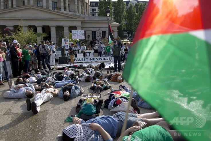 フランス首都パリ(Paris)のラ・ロトンド(La Rotonde)広場で、イスラエル軍によるパレスチナ自治区ガザ地区(Gaza Strip)攻撃の中止を求め、地面にあおむけになって抗議する人々。非政府組織(NGO)「CAPJO-EuroPalestine」による集会で、背景にある垂れ幕には「パレスチナは生きる!」と書かれている(2014年7月31日撮影)。(c)AFP/KENZO TRIBOUILLARD ▼2Aug2014AFP|「イスラエル軍は攻撃を中止せよ」、世界各地で反戦デモ http://www.afpbb.com/articles/-/3022045 #Paris #against_Israel