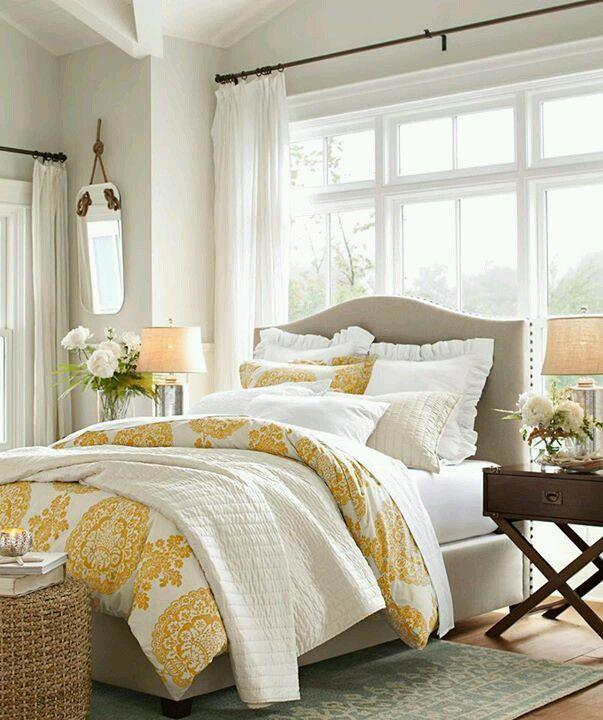 Taupe and yellow bedroom with bright windows. Guest room