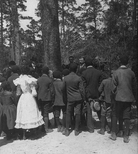 President Theodore Roosevelt speaking to a group of African American children. Early in his presidency, Roosevelt created a scandal when he invited Booker T. Washington to dine with him and his family; he was the first U.S. president ever to entertain a black man in the White House. February 5, 1906 Library of Congress