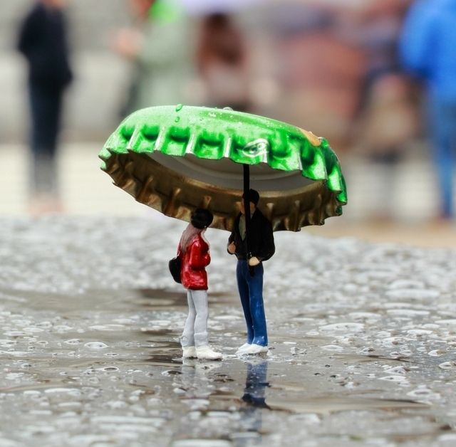Two tiny people take shelter from the rain, with inventive use of a beer bottle lid.