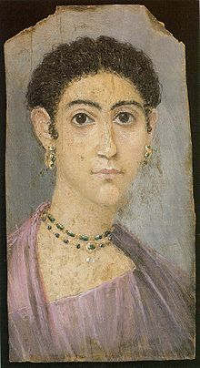 Depiction of a woman with curly hair, wearing a violet chiton and cloak and pendant earrings. British Museum.