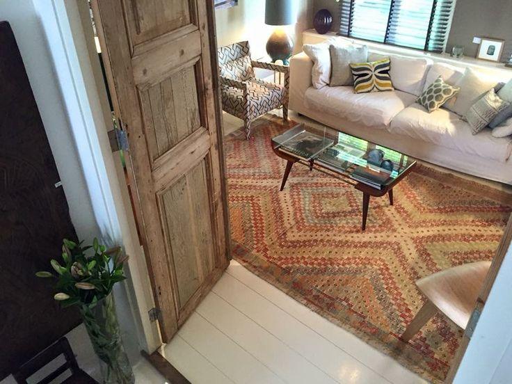 A vintage Küprübasi kilim from TRŌVE with earthy tones in a beautiful room, designed by Marbella Artisans. More info @ www.trove-shop.com