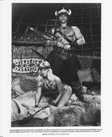 CONAN THE BARBARIAN (1982): Universal, Universal City B&W glossy publicity still #5236-C5307 of Arnold Schwarzenegger as Conan and Sandahl Bergman as Valeria, NM condition, 8 x 10 inches. $7