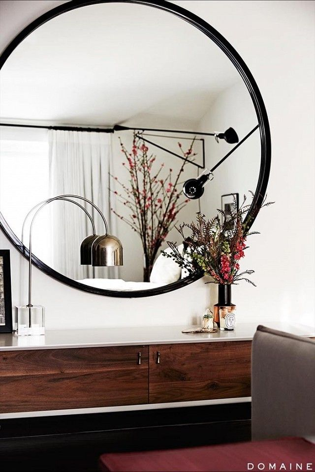 Living space with a well decorated dresser, a gold lamp, and a large mirror