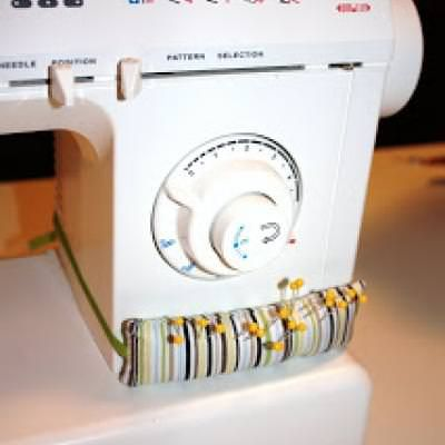 Sewing Machine Pin Cushion {Pins and Needles}This post features a cute and functional way to store your pins during a sewing project. With this tutorial you'll create a sewing machine pin cushion. All you need is a scrap of fabric, elastic and batting! View This Tutorial