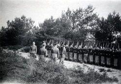 Roosendaal: Duitse militairen presenteren geweren op bospad, o.l.v. luitenant Steinert....