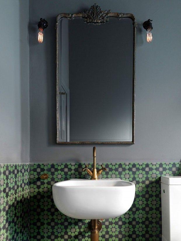 """""""Neste lavabo criativo orquestrado por Luigi Rosselli, elementos do passado ganham nova roupagem. Para começar, a parede assume um tom de cinza, que dialoga com os desenhos vintage dos ladrilhos hidráulicos. A cuba minimalista, por sua vez, é acompanhada por torneiras e canos dourados, que temperam sofisticação clássica às suas linhas puras. Um espelho antigo, com detalhes rococós, surge enferrujado.' (Foto: Divulgação) - Post do casavogue.globo.com"""