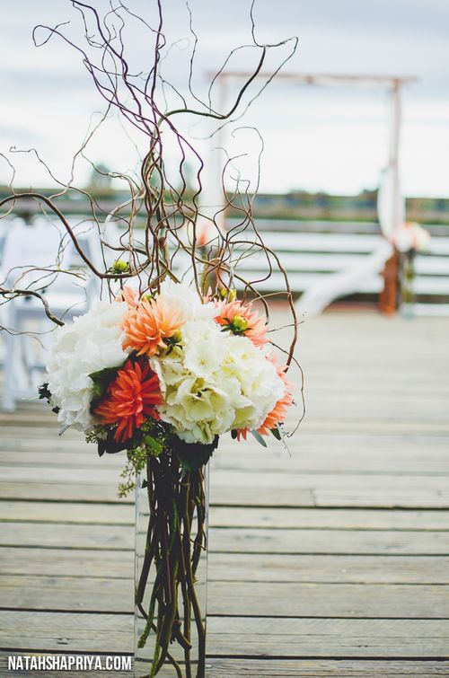 Tall wedding arrangement, coral and white, consisting of hydrangeas, dahlias, curly willow, and seeded eucalyptus www.kalosfloraldesign.com