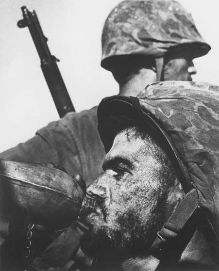 "He is here because he is so HOT!!! Photographer W. Eugene Smith's picture of a Marine drinking from his canteen during 1944's Battle of Saipan is as iconic a war picture as any ever made. In fact, when the U.S. Postal Service released a ""Masters of American Photography"" series of commemorative stamps in 2002, Smith was included - and this image was chosen as representative of his body of work."