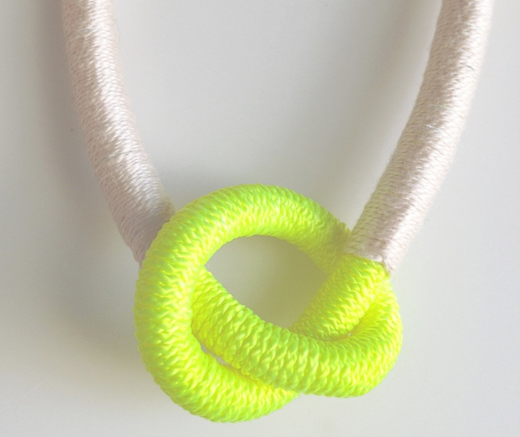 Neon yellow knot necklace wrapped in light pink thread.