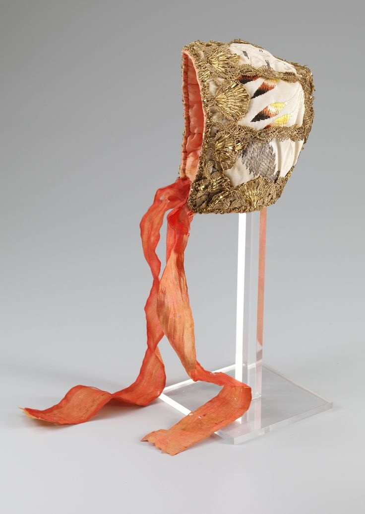 Child's cap, Norway, 1740-1800. Cream silk brocade, metall lace decoration, orange silk lining, orange silk ribbon binding.
