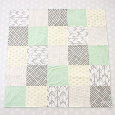 This modern baby quilt comes in a soft and neutral mix of gray, mint, and gold prints with various triangle, line, and arrow patterns. Our Mason's Mint & Gold Arrow Baby Quilt is the perfect baby shower gift and a must have for an on the go spot to safely lay your baby down.