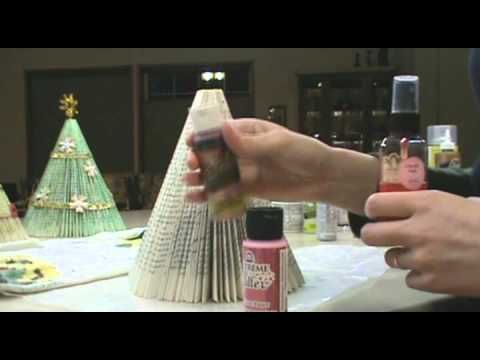 This is a tutorial on how to make a Holiday Tree from a paperback book: one paperback book with at least 150 pages, binder clips (large size work best), glitter paint or spray on glue and loose glitter, brushes (if using glitter paint), scissors, hot glue gun and glue sticks, ribbons, gems, bows, tinsel, pipe cleaners, paper flowers, etc.