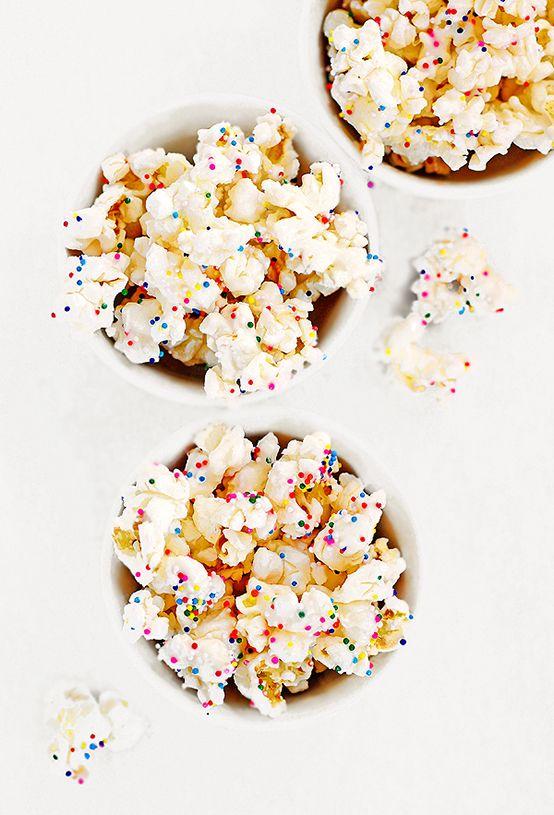 Zo maak je popcorn extra feestelijk, witte gesmolten chocolade over de popcorn en dan gekleurde sprinkels erover strooien :-)