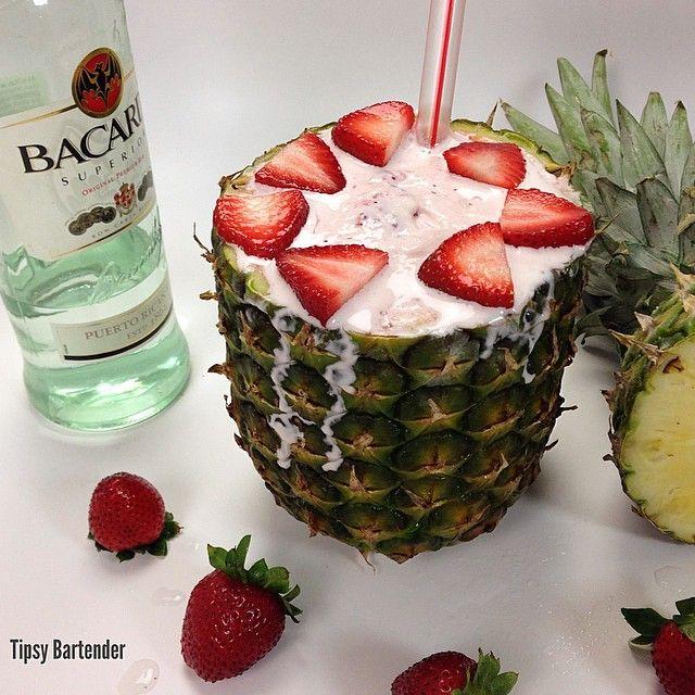 Strawberry Pina Colada ~ 1 Pineapple, 1 1/2 oz. (45ml) White Rum, 1 1/2 oz. (45ml) Cream of Coconut, 1 1/2 oz. (45ml), Pineapple Juice, 2 Scoops Strawberry Ice Cream, Strawberry Slices