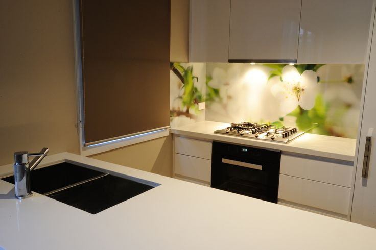 This printed glass splashback works  really well to break up this predominantly white kitchen and at the same time making it unique!