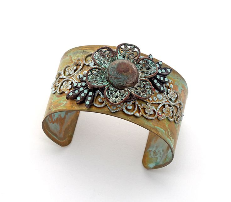 Statement button cuff, Victorian/Shabby Chic/Southwestern genres, with an exquisite vintage antique bronze brass filigree flower button. Swarovski blue opalescent crystal chatons have been meticulously handset in Art Deco era brass components. Patinaed brass filigree adds a lacy layer to the gold and turquoise patinaed brass cuff, further enhancing the feminine appeal of this design.  This cuff measures 1-1/2 inch (3.8 cm) wide and will fit most.