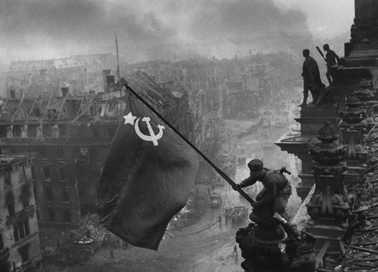 Soviet Union soldiers Raqymzhan Qoshqarbaev, and Georgij Bulatov raising the flag on the roof of Reichstag building in Berlin, Germany in May, 1945. The photograph was taken by Yevgeny Khaldei.