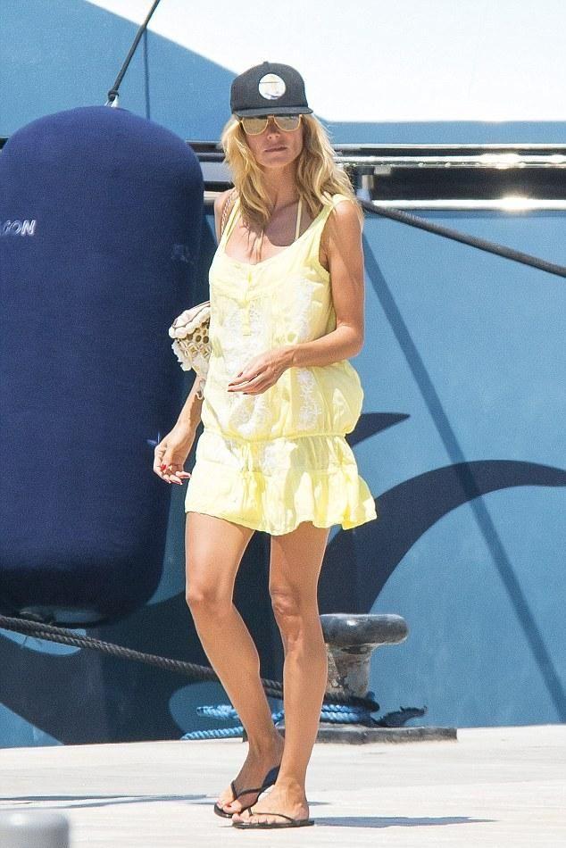 Heidi Klum wearing Tkees Gloss Flip Flops in Licorice, Figue Tuk Tuk Bag, Eres Alliages Zinc and Nickle Triangle Bikini and Melissa Odabash Jaz Dress