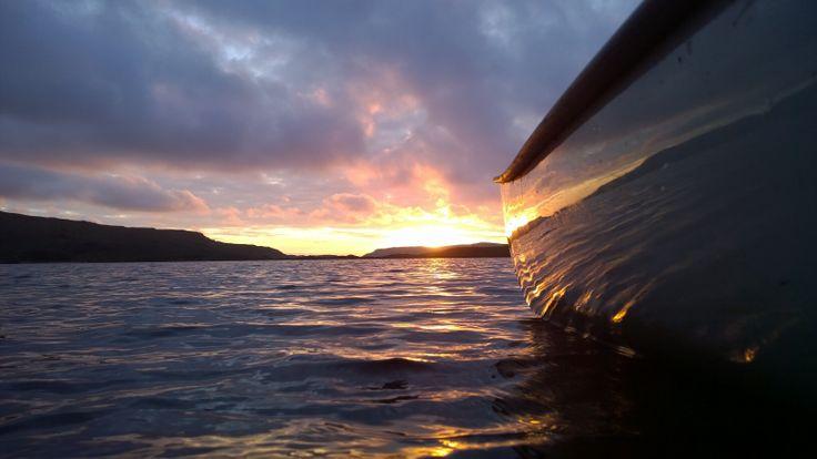 Sun setting near Summer Isles, reflected on the side of the canoe on Loch Lurgainn