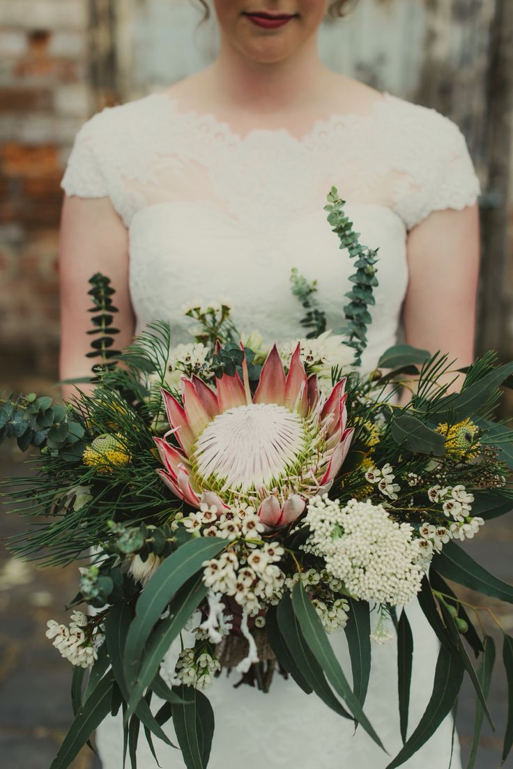 Australian native, protea, eucalyptus bridal bouquet. Sweet heart, short sleeve, lace wedding dress