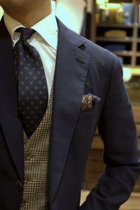 ネイビーのスーツに千鳥格子柄のツイードベストを組み合わせたコーデ