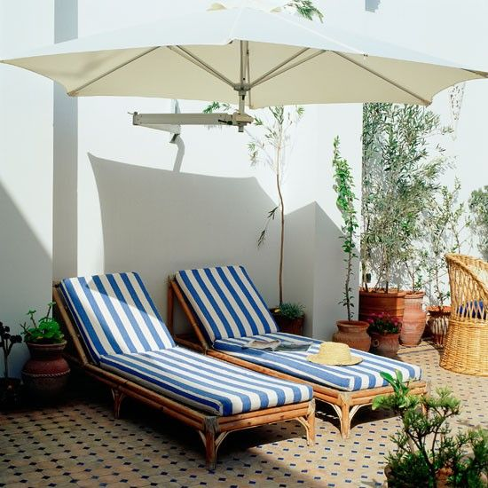 Comfy garden seating    Find a sun trap in your garden and place two large sun loungers side by side for a relaxing spot. Add a wall-mounted parasol that will provide essential shade.    Lounger  Marks & Spencer  Parasol  Garden and Leisure
