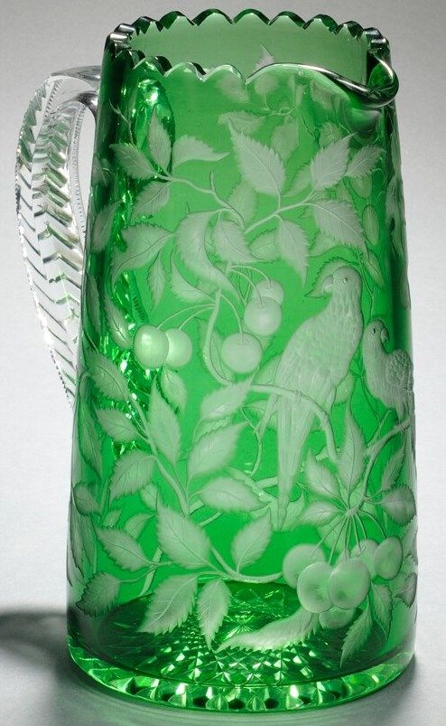 An American green cut- to-clear and engraved glass pitcher, attributed to Dorflinger, with scalloped rim, tapering body engraved with two parrots perched among fruiting cherry tree branches, cut hobstar to underside, and applied handle. circa 1901-1925
