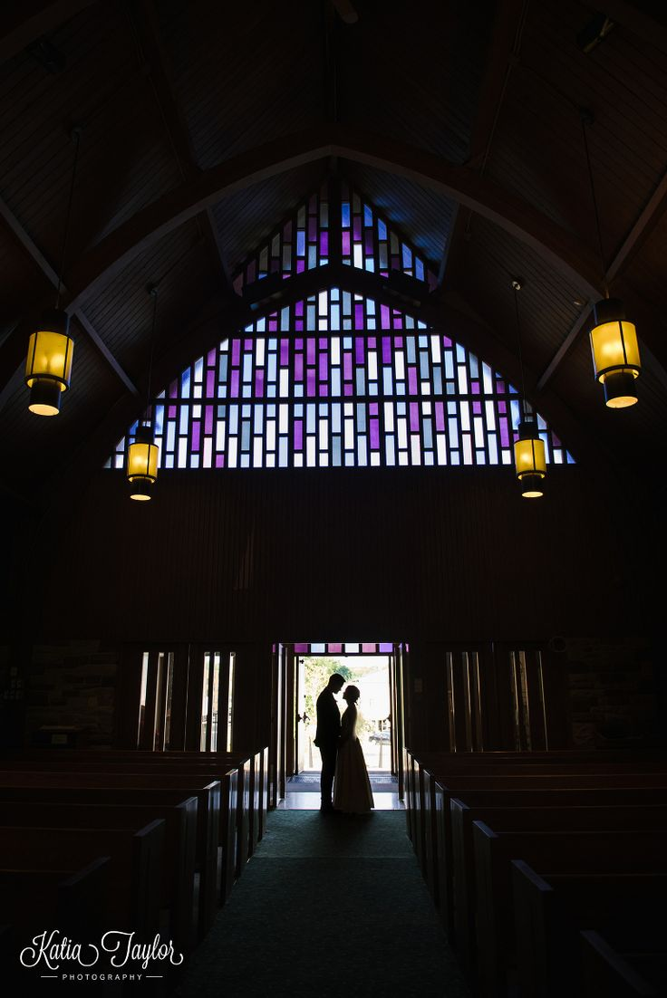 Silhouette of bride and groom in church door with beautiful stained glass windows. St. Giles Kingsway Presbyterian Church. Toronto.