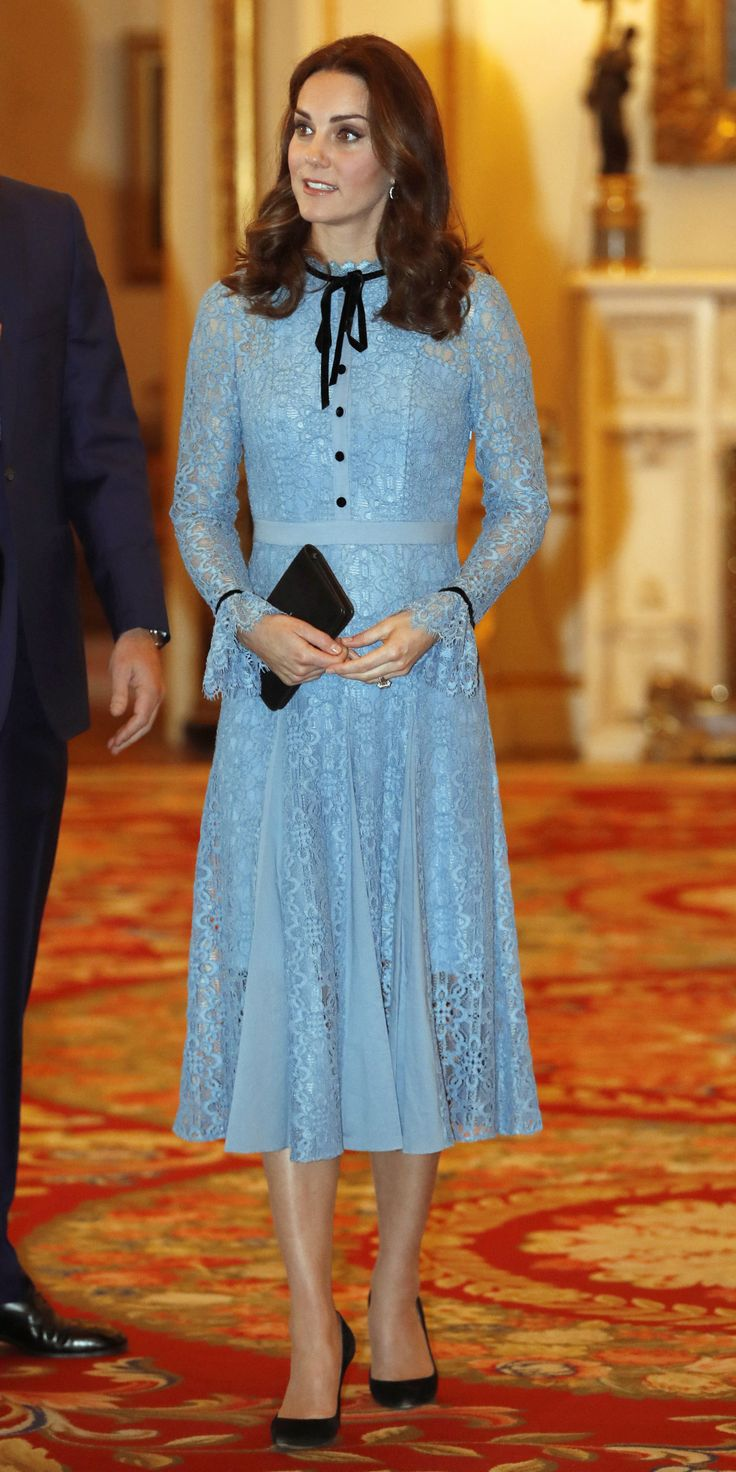 Kate Middleton is back. In her first public appearance since making her third pregnancy announcement, the Duchess of Cambridge stepped out for a reception in honor of World Mental Health Day, wearing an undeniably gorgeous blue dress. The Temperley London gown featured sheer lace sleeves, a figure-defining belt, and contrasting black buttons and trim. Classic black accessories and glimmering diamond jewelry completed the look.