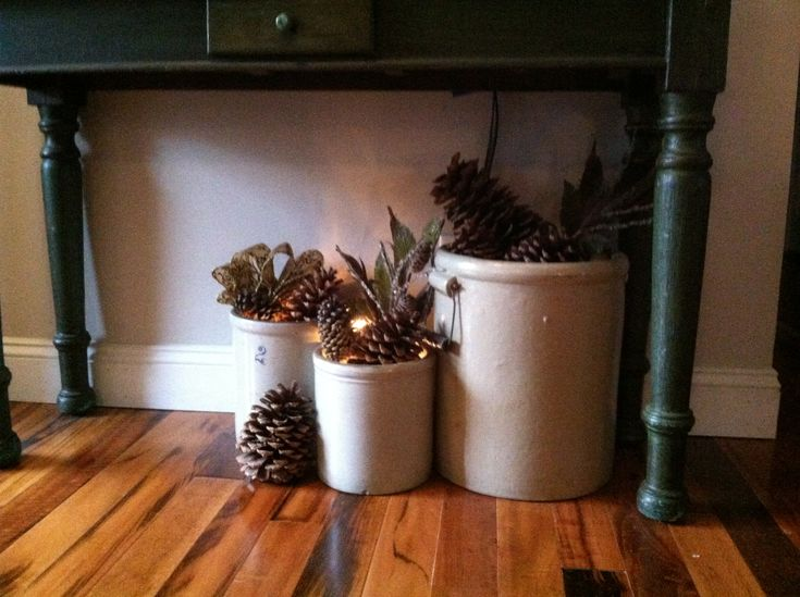 I love to fill my crocks with seasonal decor. Pinecones, wintry picks, and a strand of lights really makes this a cozy little nook