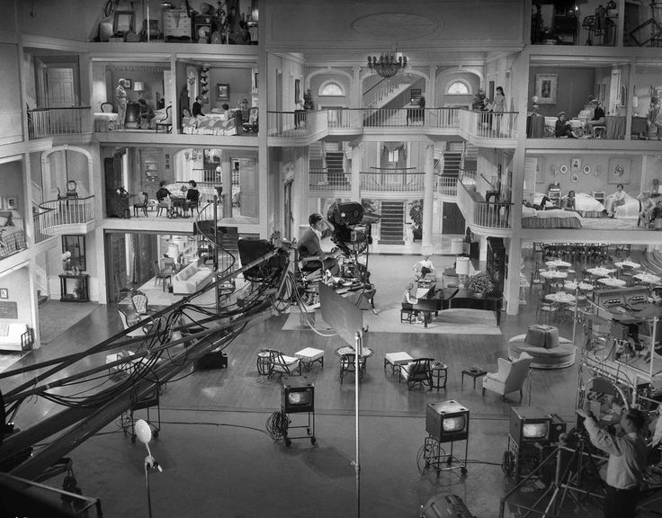 """Co-writer/director/star Jerry Lewis (sitting behind camera center) prepares a shot on the massive set of """"The Ladies' Man"""", 1961.  Lewis build this set with independent lighting and sound on each of the levels and had to adjoin two soundstages to do so.  Note the video monitors below the camera."""